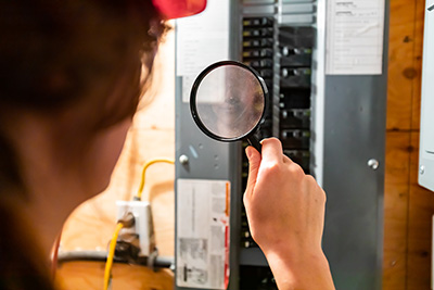 selective focus on inspector woman's hand holding a magnifying glass in the front of home Distribution panel board. house electrical systems check